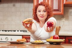 Big woman eat fast food. Red hair fat girl with burger, potato a. Nd fruit. Unhealthy food concept with plus size female on kitchen royalty free stock photos