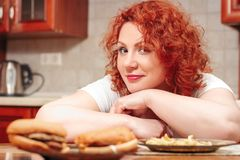 Big woman eat fast food. Red hair fat girl with burger, potato a. Nd fruit. Unhealthy food concept with plus size female on kitchen royalty free stock photography