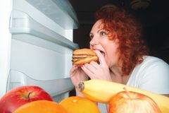Big woman eat fast food. Red hair fat girl looking inside refrigerator with burger. Unhealthy and healthy food concept with plus. Size female on kitchen stock photography