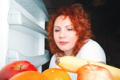 Big woman eat fruit. Red hair fat girl looking inside refrigerator. Unhealthy and healthy food concept with plus size female on k. Itchen stock images