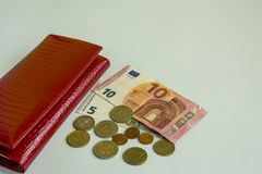 Big woman red wallet. Banknotes of 5 and 10 euros. Some coins. Blue background stock image