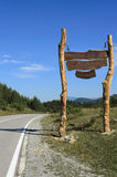 Big wood sign by the road on the mountain Royalty Free Stock Image