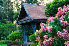 Big wooden asian country style pavilion in the beautiful garden. With flowers. Selective focus Royalty Free Stock Image
