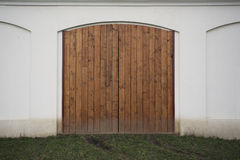 Big wooden barn gate. Monumental farm door, two timber leaf, closed brown gateway with planks and nails Royalty Free Stock Photography