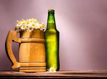 Wooden beer mug with fine daisies similar to foam and a green full bottle with a metal lid. Big wooden beer mug with chamomiles similar to foam and a green full royalty free stock photography