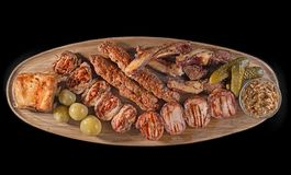 Big wooden board with assorted meats, preferably served as companion for beer or other alcohol drinks Royalty Free Stock Image