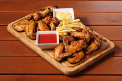 Big wooden board with grilled chicken winds Stock Photography