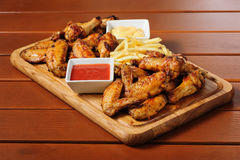 Big wooden board with grilled chicken winds Royalty Free Stock Photos