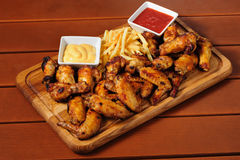 Big wooden board with grilled chicken winds Stock Photos