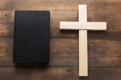 Big wooden Christian cross near the Bible. A big wooden cross next the closed Holy Bible. A black book on a wooden surface. The way to God through prayer stock photos