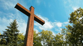 Big Wooden Cross Standing among Trees on the background of Sky and Moving Clouds. Big Wooden Cross is Standing among the Trees on the background of Blue Sky and stock video