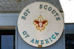 Big wooden sign on a building stating Boy Scouts of America. A big wooden sign is attached to a building and states, `Boy Scouts of America` with the boy scout Stock Images