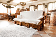 Big wooden sofa with white blanket Stock Photography