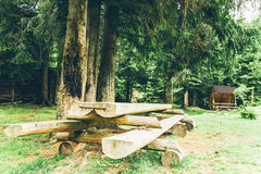 Big wooden table in the middle of the forest. In carpathian mountains Stock Image