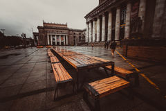 Big wooden table under The Palace of Culture and Science. Big wooden table in front of The Palace of Culture and Science in rain Royalty Free Stock Photography