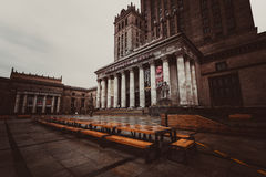 Big wooden table under The Palace of Culture and Science. Big wooden table in front of The Palace of Culture and Science in rain Royalty Free Stock Photos