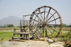 Big wooden turbine baler water wheel at Thai Dam Cultural Village. Big wooden turbine baler water wheel or wood noria water with landscape rice field mountain at royalty free stock photos