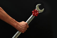 Big Wrench With Christmas Bow. Man holding a big wrench with a red christmas bow Stock Photography