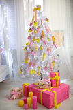 Big xmas tree. White studio light room design decorative x-mas tree, big hall prepare and decorated for Christmas & New Year party. Big candy balls and presents Royalty Free Stock Photos