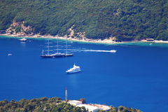 Big yacht on blue water near shore. Very big and exclusive sailing yacht on blue water from a Montenegro`s bay, with forested hills and some small boats Royalty Free Stock Photography