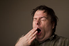 Big yawn. MAn lets out a huge yawn with how tired he is, or is he getting ready to sneeze Stock Image