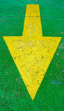 Big yellow arrow pointing down with green background Royalty Free Stock Photos