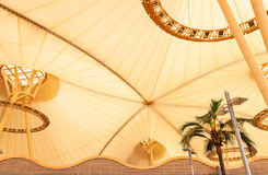 Big yellow canvas tent roof with palm tree in tropics Stock Images