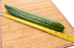 Big yellow centimeter and big green cucumber. Big yellow industrial meter and big green fabio cucumber on a bamboo board royalty free stock photos