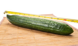 Big yellow centimeter measuring a green cucumber. Big yellow centimeter measuring a big fabio cucumber on a bamboo plate with white background stock image