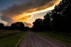 Big Yellow Cloud at Dusk Dirt Road Disappearing Into Disatance stock photography