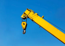 Big yellow construction crane. On blue sky background Stock Images