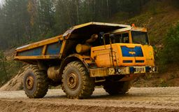Big yellow diesel quarry dumper at work. Heavy mining truck transporting sand and clay. Belaz stock images