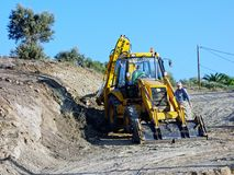 Big Yellow Digger Excavating New Dirt Road. A big yellow digger excavating new dirt road leading to new building site, Greece royalty free stock image