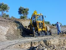 Big Yellow Digger Excavating New Dirt Road. A big yellow digger excavating new dirt road leading to new building site, Greece stock images