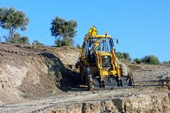 Big Yellow Digger Excavating New Dirt Road. A big yellow digger excavating new dirt road leading to new building site, Greece royalty free stock images