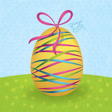 Big yellow easter egg with colorful ribbons Stock Images