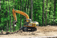 Big yellow excavator near the forest Royalty Free Stock Photos