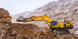 Big yellow excavator. At an open pit mining Stock Photos