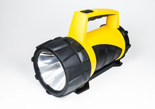 Big yellow flashlight hand held with adjustable angle isolated on white background.. Stock Image