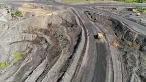 Big yellow heavy truck in open cast mine mining of coal the overall plan. Open pit anthracite mining, mining truck at