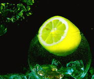 Big yellow lemon and ice inside glassball with w. Big yellow lemon with six inside segments  and ice inside glassball with water air drop on black background Royalty Free Stock Image