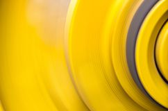 Big yellow pulleys. Big yellow pulleys are rapidly rotating by being driven by a conveyor belt royalty free stock photography