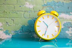 Big yellow retro style alarm clock. Decorated in a living room with colorful brick wall royalty free stock photography