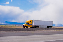 Big yellow rig semi truck trailer on highway in Utah Stock Photo
