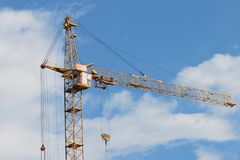 Big yellow stationary hoist on construction site. Blue sky and white clouds Stock Images