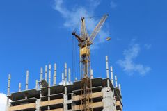 Big yellow stationary hoist on construction site. Part of building, blue sky and white clouds Royalty Free Stock Photos