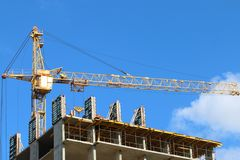 Big yellow stationary hoist on construction site. Part of building at sunny day Royalty Free Stock Photo