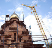Big yellow tower crane on russian church constructions Stock Photos