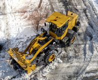 Big yellow tractor cleaning road. Bulldozer remove snow from the street. Snowplow in city, sunny winter day. View from above Stock Images