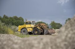 Big yellow tractor. Big heavy tractor on construction site Stock Photos